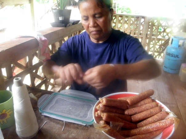 Here's Penny linking sausages. We use commercial sausage casings because we don't have enough of our own casings. Often, pork intestines are cooked in the popular pork blood stew called